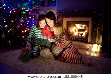 Happy young mother and her two small daughters opening a magical Christmas gift by a fireplace in a cozy dark living room on Christmas eve. Winter evening at home with family and kids. #1531000445