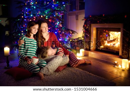 Happy young mother and her daughters having a good time sitting together by a fireplace in a cozy dark living room on Christmas eve. Celebrating Xmas at home. Winter evening with family and kids. #1531004666