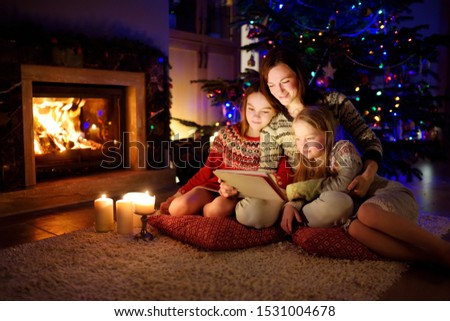 Mother and her two cute young daughters using a tablet pc at home by a fireplace in warm and cozy living room on Christmas eve. Winter evening at home with family and kids. #1531004678