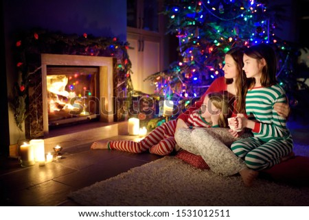 Happy young mother and her daughters having a good time sitting together by a fireplace in a cozy dark living room on Christmas eve. Celebrating Xmas at home. Winter evening with family and kids. #1531012511