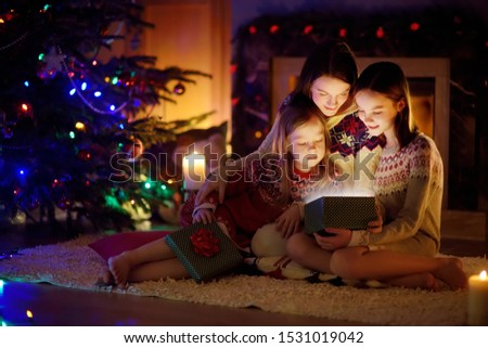 Happy young mother and her two small daughters opening a magical Christmas gift by a fireplace in a cozy dark living room on Christmas eve. Winter evening at home with family and kids. #1531019042