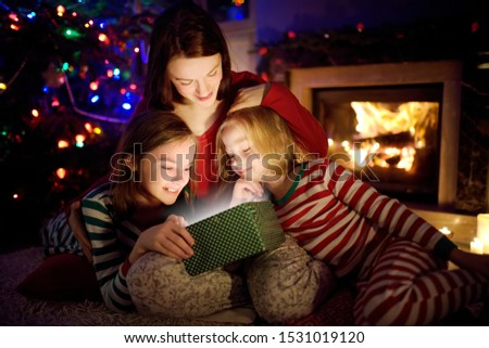 Happy young mother and her two small daughters opening a magical Christmas gift by a fireplace in a cozy dark living room on Christmas eve. Winter evening at home with family and kids. #1531019120
