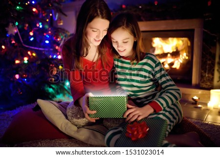 Happy young mother and her young daughter opening a magical Christmas gift by a fireplace in a cozy dark living room on Christmas eve. Winter evening at home with family and kids. #1531023014