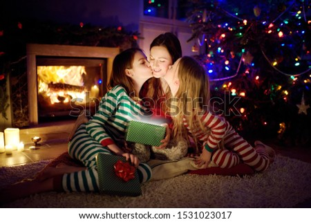 Happy young mother and her two small daughters opening a magical Christmas gift by a fireplace in a cozy dark living room on Christmas eve. Winter evening at home with family and kids. #1531023017