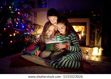 Happy young mother and her two small daughters opening a magical Christmas gift by a fireplace in a cozy dark living room on Christmas eve. Winter evening at home with family and kids. #1531023026