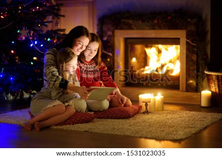 Mother and her two cute young daughters using a tablet pc at home by a fireplace in warm and cozy living room on Christmas eve. Winter evening at home with family and kids. #1531023035