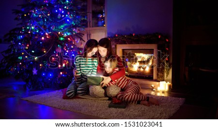 Happy young mother and her two small daughters opening a magical Christmas gift by a fireplace in a cozy dark living room on Christmas eve. Winter evening at home with family and kids. #1531023041