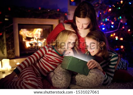 Happy young mother and her two small daughters opening a magical Christmas gift by a fireplace in a cozy dark living room on Christmas eve. Winter evening at home with family and kids. #1531027061