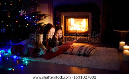 Happy young mother and her daughters reading a story book together by a fireplace in a cozy dark living room on Christmas eve. Celebrating Xmas at home. Winter evening with family and kids. #1531027082