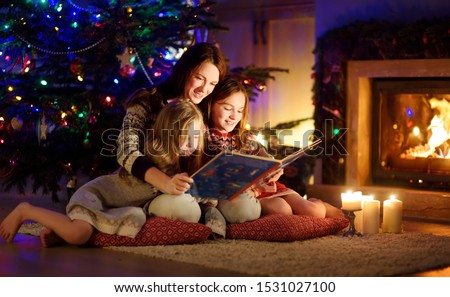 Happy young mother and her daughters reading a story book together by a fireplace in a cozy dark living room on Christmas eve. Celebrating Xmas at home. Winter evening with family and kids. #1531027100