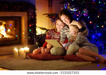 Mother and her two cute young daughters using a tablet pc at home by a fireplace in warm and cozy living room on Christmas eve. Winter evening at home with family and kids. #1531027103