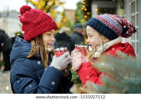 Two adorable sisters drinking hot chocolate on traditional Christmas fair in Riga, Latvia. Children enjoying sweets, candies and gingerbread on Xmas market. Winter time with family and kids. #1531027112