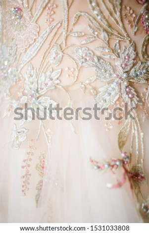 Bead embroidery on the white laces with pink and blue threads. Wedding dress decoration. #1531033808