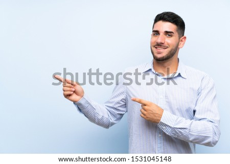 Caucasian handsome man over isolated blue background pointing finger to the side #1531045148