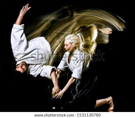 two budokas fighters man and woman practicing Aikido studio shot isolated on black background Royalty-Free Stock Photo #1531130780