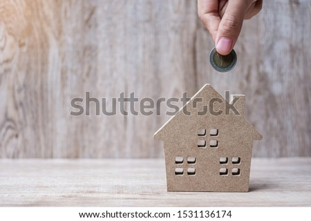 Man hand putting coin over house model on wooden background. Banking, real estate, investment, success, financial and savings concepts #1531136174