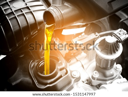 Refueling and pouring oil quality into the engine motor car Transmission and Maintenance Gear .Energy fuel concept. #1531147997