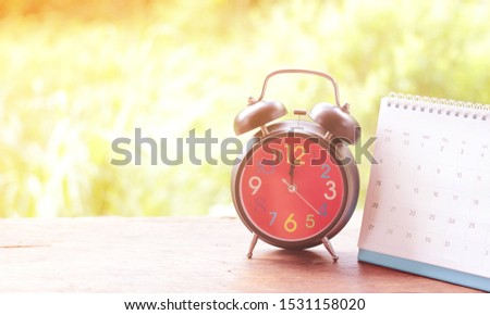 Black antique alarm clock on a wooden table and a light background calendar. #1531158020