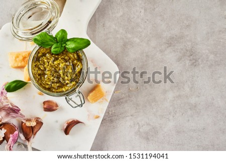 Pesto sauce or pesto genovese in a glass jar with pine nuts, parmesan, basil, oil and garlic on white marble cutting board over grey stone background. Top view. Copy space. #1531194041