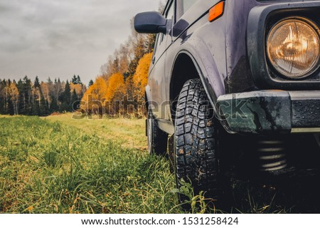 Wheels of an SUV on wet, fading grass at the edge of a forest in the Russian outback on a cloudy autumn day. Adventures to overcome the inaccessible forests. #1531258424