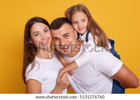 Horizontal shot of happy family wearing white shirts, stand smiling isoalted over yellow studio background, father piggybacking her adorable female kid. Relationship, happyness and devotion concept.