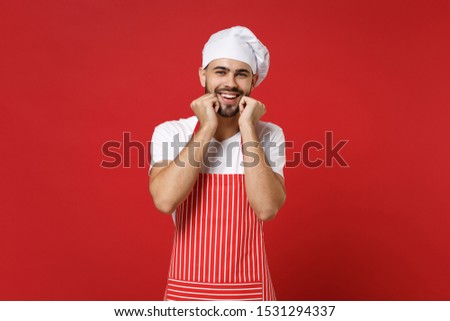 Joyful young bearded male chef cook or baker man in striped apron white t-shirt toque chefs hat posing isolated on red background in studio. Cooking food concept. Mock up copy space. Clenching fists #1531294337