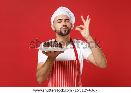 Bearded male chef cook or baker man in striped apron toque chefs hat posing isolated on red background. Cooking food concept. Mock up copy space. Hold plate with cake, making okay taste delight sign #1531294367