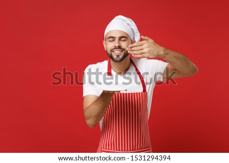 Chef cook or baker man in striped apron toque chefs hat isolated on red background. Cooking food concept. Mock up copy space. Holding plate with place for food raised hand to face, feeling food smell #1531294394