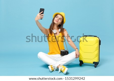 Traveler tourist woman in yellow casual clothes hat with suitcase photo camera isolated on blue background. Female passenger traveling abroad travel on weekends getaway. Air flight journey concept #1531299242