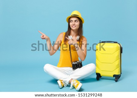 Traveler tourist woman in yellow casual clothes hat with suitcase photo camera isolated on blue background. Female passenger traveling abroad to travel on weekends getaway. Air flight journey concept #1531299248
