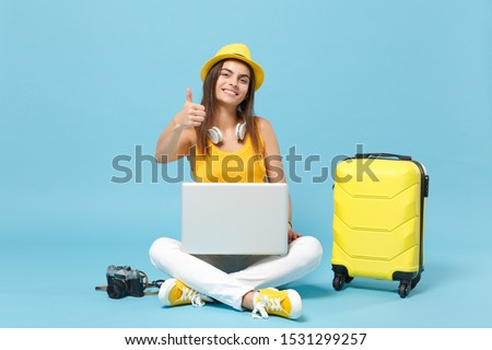 Traveler tourist woman in yellow casual clothes, hat with suitcase laptop pc photo camera isolated on blue background. Female passenger traveling abroad travel on weekends. Air flight journey concept #1531299257