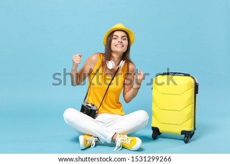 Traveler tourist woman in yellow casual clothes hat with suitcase photo camera isolated on blue background. Female passenger traveling abroad to travel on weekends getaway. Air flight journey concept #1531299266