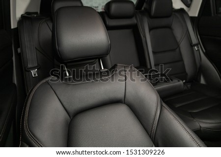 Close-up rear seat made of black leather with a head restraint, in the background passenger seats with seat belts. Luxury car interior Royalty-Free Stock Photo #1531309226