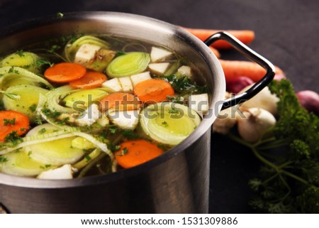 Broth with carrots, onions various fresh vegetables in a pot - colorful fresh clear spring soup. Rural kitchen scenery vegetarian bouillon or stock