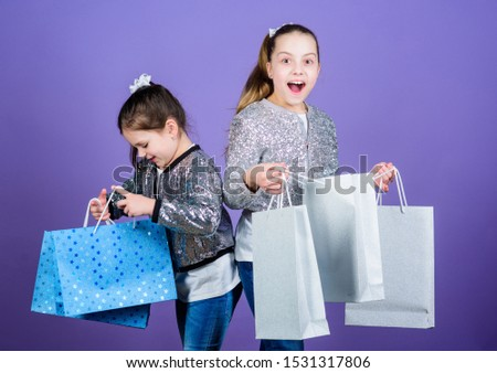Black friday. Sale and discount. Shopping day. Children bunch packages. Kids fashion. Girls sisters friends with shopping bags violet background. Because image is everything. Shopping and purchase.