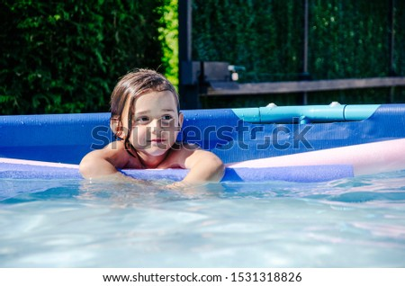 A girl caucasian enjoys playing in the home pool #1531318826