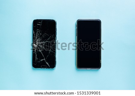 Modern touch screen smartphone with broken screen and new one on blue background, top view