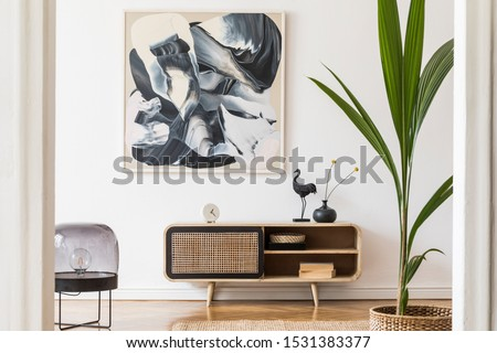 Scandinavian and design home interior of living room with wooden commode, design black lamp, rattan basket, plants and elegant accessories. Stylish home decor. Template. Mock up poster paintings.  #1531383377