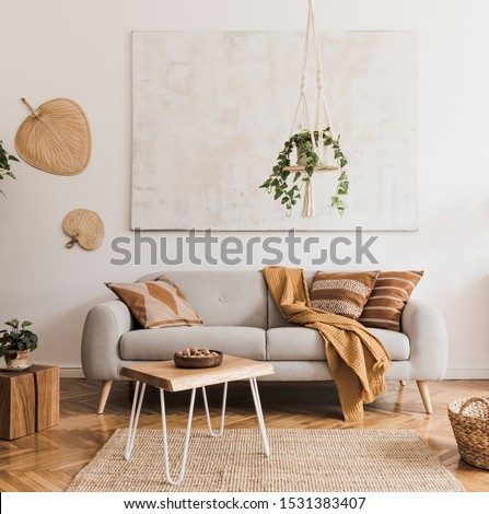 The stylish boho compostion at living room interior with design gray sofa, wooden coffee table, commode and elegant personal accessories. Honey yellow pillow and plaid. Cozy apartment. Home decor #1531383407