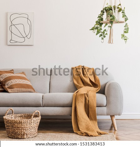 Modern boho interior of living room at cozy apartment with gray sofa, honey yellow pillows and plaid, plants, paintings, rattan basket and design personal accessories. Stylish home decor. Template. #1531383413