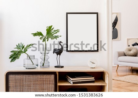 Modern scandinavian home interior with mock up photo frame, design wooden commode, black sculpture, tropical leaf, gray sofa and personal accessories. Stylish home decor. Template. Ready to use.  #1531383626