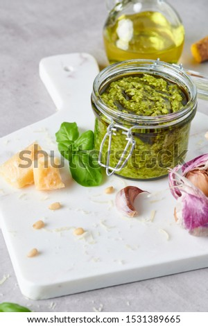 Pesto sauce or pesto genovese in a glass jar with pine nuts, parmesan, basil, oil and garlic on white marble cutting board. Copy space. #1531389665