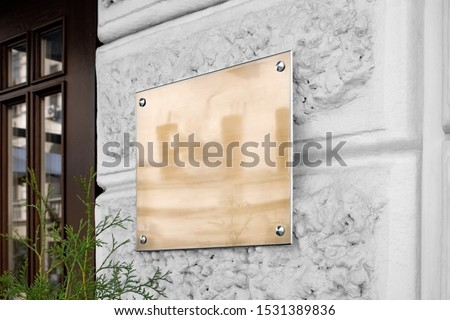Blank gold glass signboard on textured wall mock up. Empty company nameboard mockup. Clear luxury acrylic sign board on building for business logotype mokcup template.