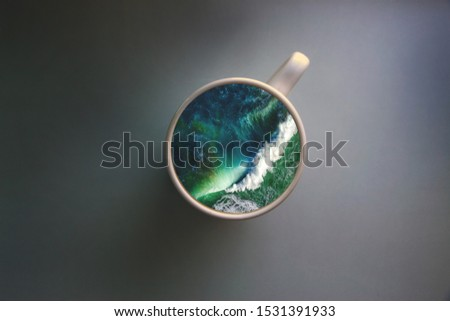 White cup with water. Sea. Ocean. Sea waves. Creative postcard. #1531391933