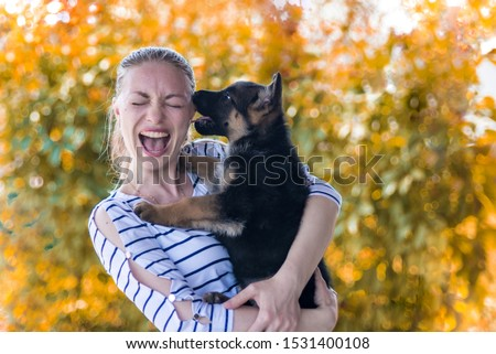 Portrait. Happy girl holding a German shepherd puppy and smiling. Buying and acquiring a dog, the joy of meeting an animal. Funny watchdog bites the owner. On a yellow autumn background. copy space #1531400108