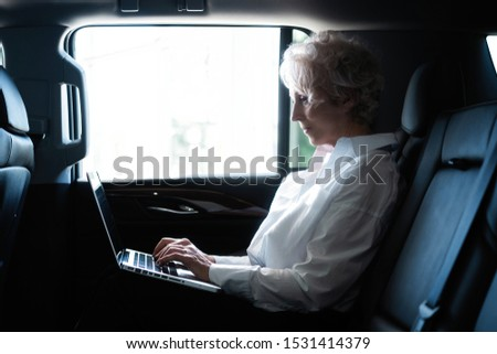 Senior businesswoman travelling to office in a car sitting on backseat with laptop. Businesswoman with laptop receiving a mail on the backseat of a car. #1531414379