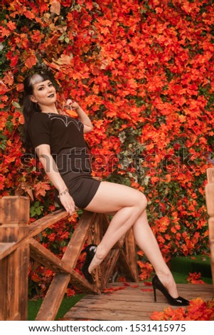beautiful girl in a black corset and lace tights sits on the bridge in the autumn Park among the orange leaves #1531415975