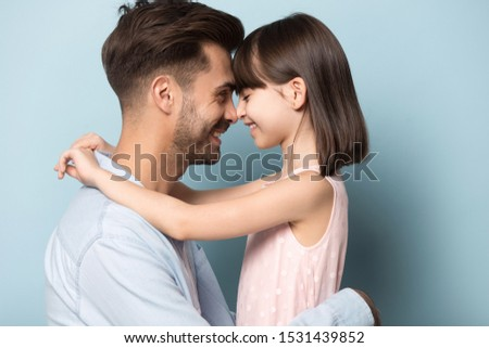 Close up portrait of young dad and preschool daughter stand isolated on blue studio background hug touch forehead noses, happy father and girl child share tender moment together show love care #1531439852