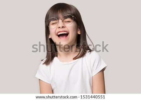 Overjoyed cute small preschooler girl in glasses isolated on grey studio background feel happy laugh at funny joke, smiling little child in spectacles excited with good sight correction at opticians