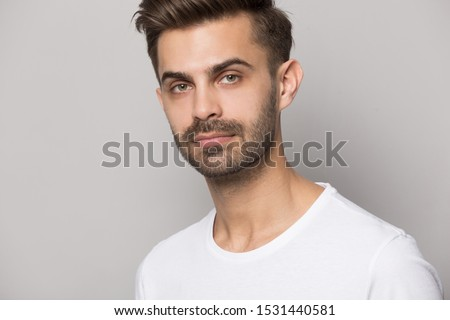 Close up headshot portrait of serious caucasian man in white t-shirt isolated on grey studio background posing, concentrated young businessman entrepreneur look at camera, model portfolio shooting